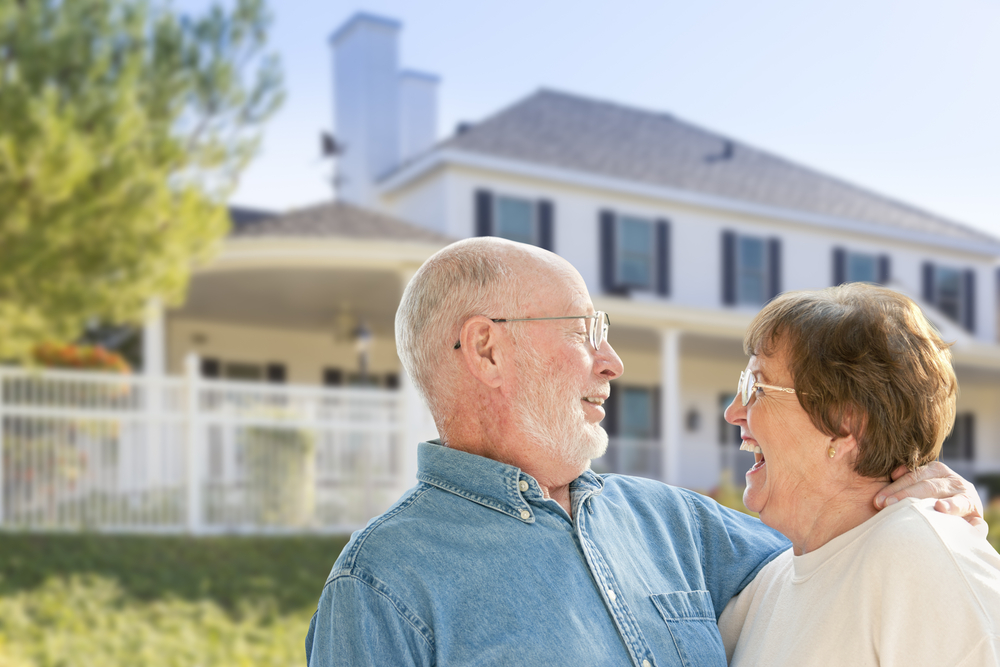 Happy seniors couple in front of their new home